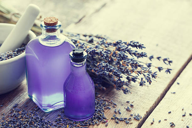 Two bottles of essential oil, mortar and lavender flowers. – Foto