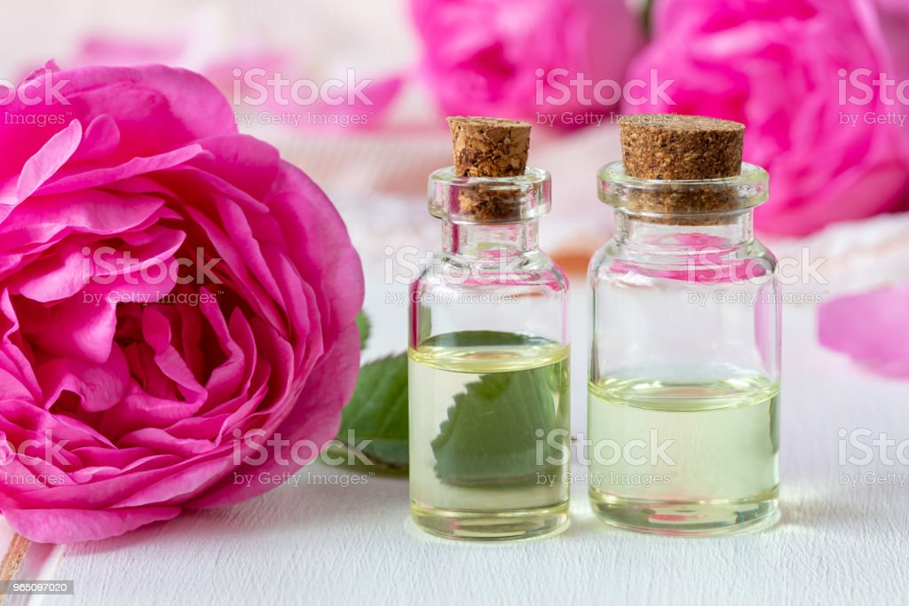 Two bottles of essential oil with fresh roses zbiór zdjęć royalty-free