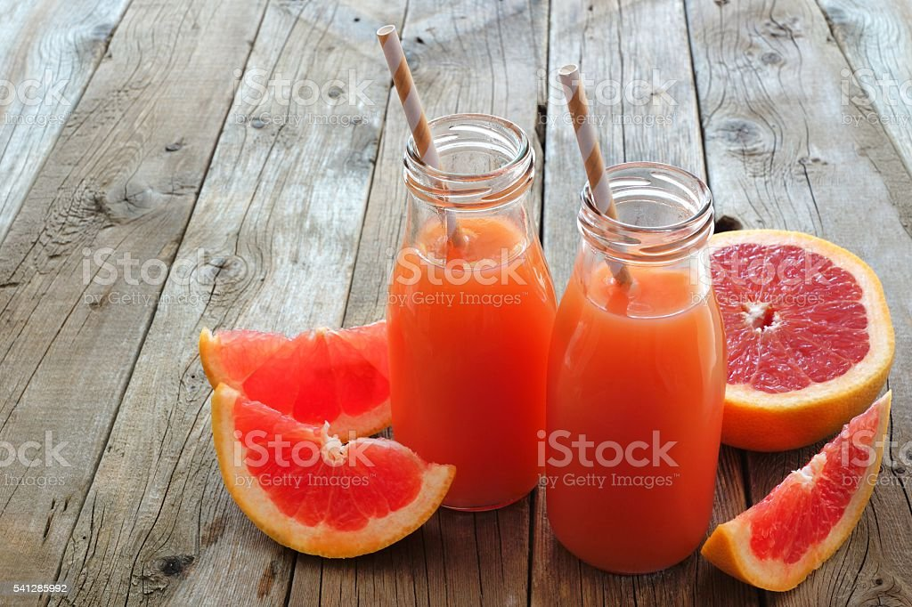 Two bottles of grapefruit juice on rustic wooden background stock photo