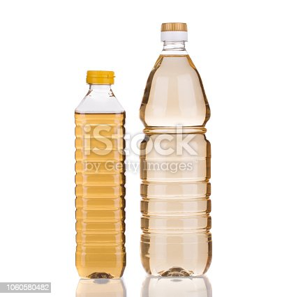 Two bottles of vinegar. It is isolated in a white background. Close-up.