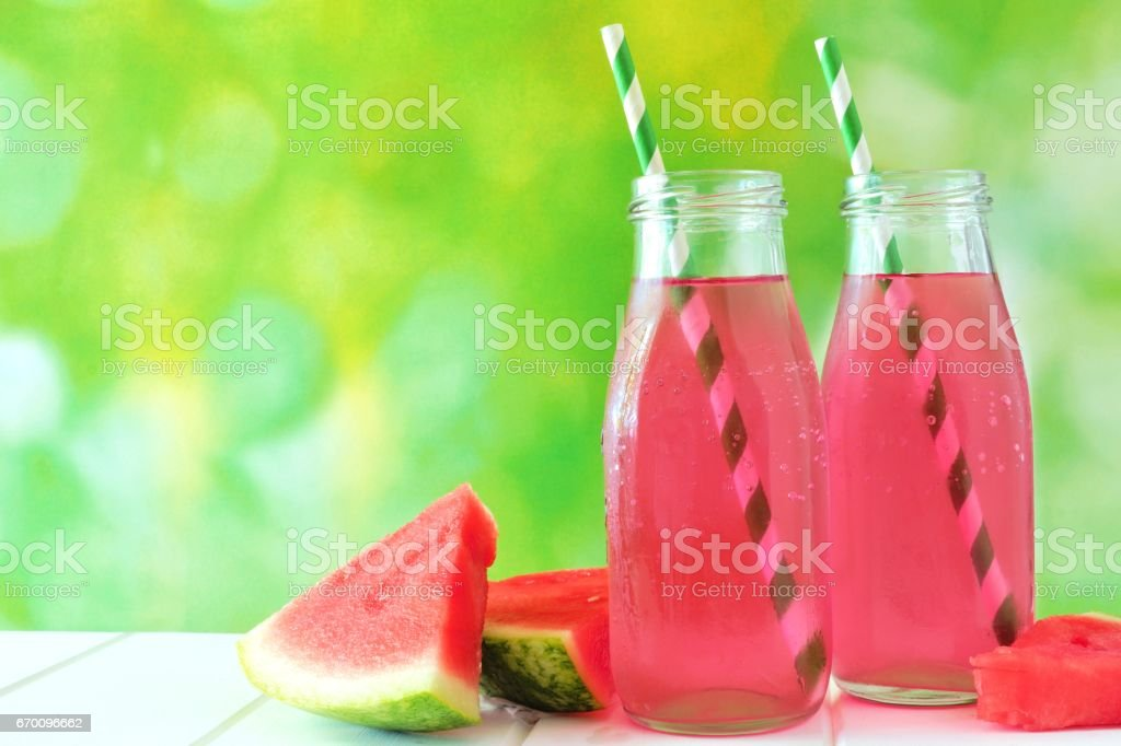 Two bottles of watermelon juice with green outdoor background stock photo