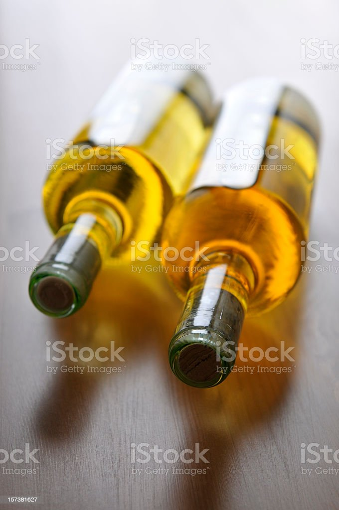 Two bottles with sweet white wine lying on wooden table royalty-free stock photo