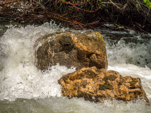 Two boulders surrounded by rushing water stock photo