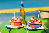 Two bowls of Bahamian conch salad set on a green table