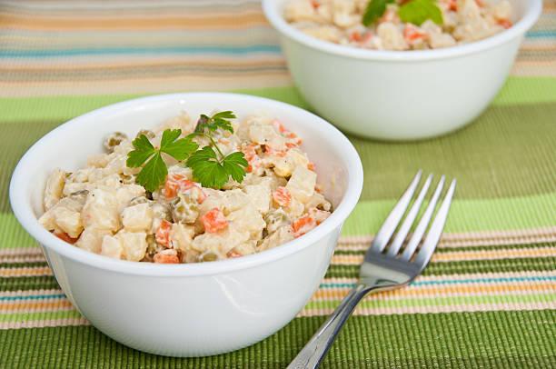 Two bowls of potato salad on green napkin stock photo
