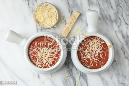 An overhead close up horizontal photograph of two bowls full of roasted tomato soup garnished with freshly grated parmesan cheese and a bowl of grated parmesan cheese.