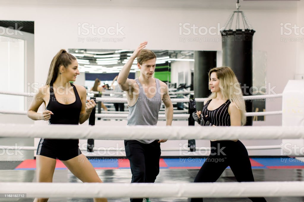 Two boxer women greet each other before fight, their young handsome...