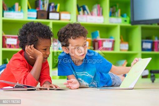 istock Two boy kid lay down on floor and reading tale book  in preschool library,Kindergarten school education concept 832178230