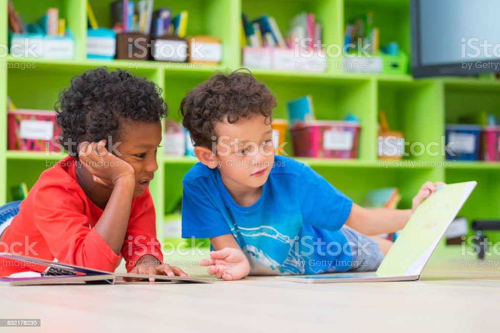 Two boy kid lay down on floor and reading tale book  in preschool library,Kindergarten school education concept - foto stock