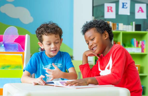 zwei junge kind sitzen am tisch und lesen märchen buch im vorschulalter bibliothek, kindergarten schule bildungskonzept - leseunterricht stock-fotos und bilder