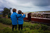 Two boy, looking at old steam train, outdoor