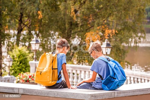 Two kids after school, sitting on bench and talking