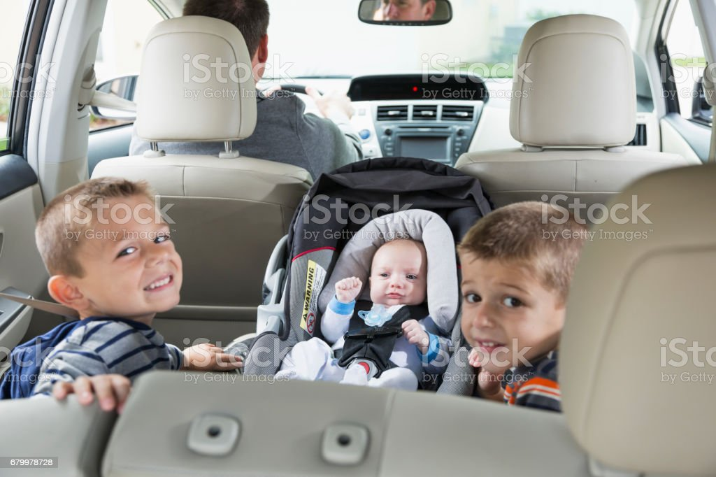 Two boys and baby in back seat of car, father driving stock photo