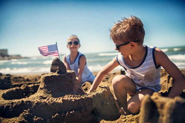 Two boys are building a sandcastle on beach stock photo
