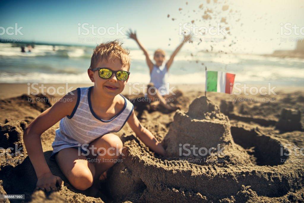 Zwei jungen bauen eine Sandburg am Strand von italienischen – Foto
