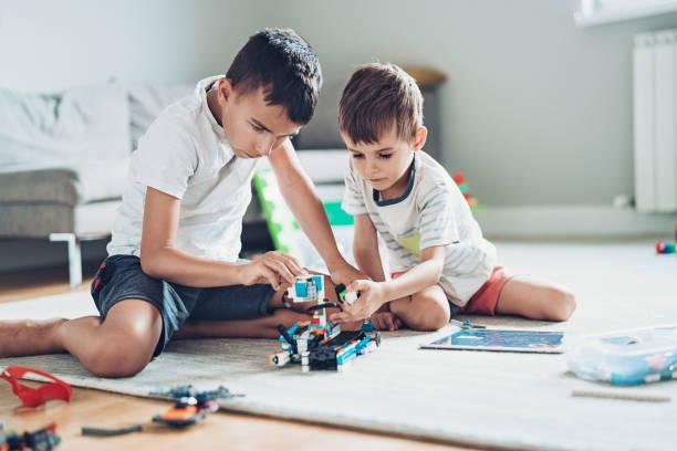 Zwei Jungen bauen einen Roboter aus Kleinteilen – Foto