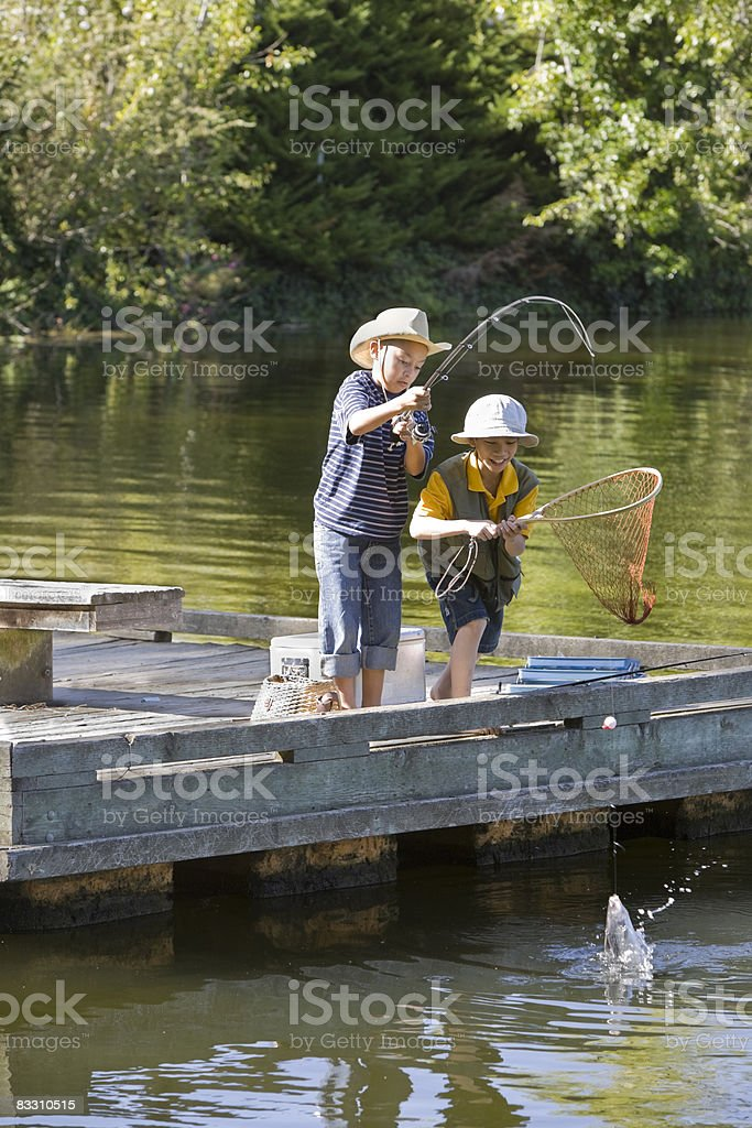 Two boys catching a fish at a lake foto stock royalty-free