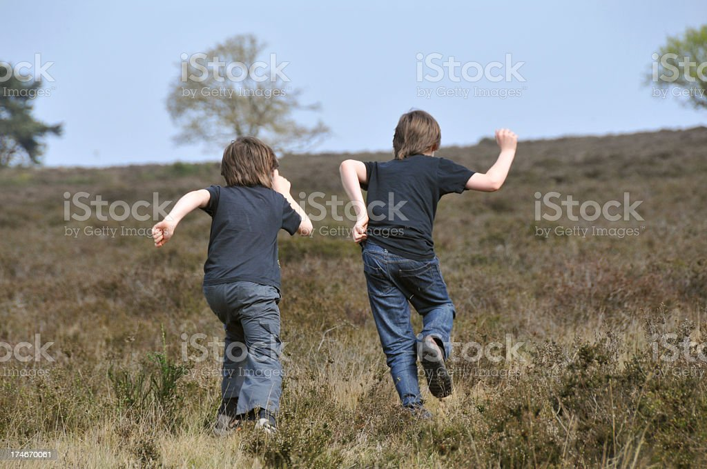 Two boys, children,  running oudoors in  heather stock photo