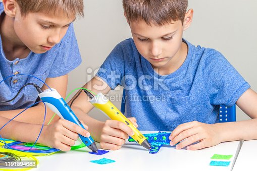 1082038948 istock photo Two boys creating with 3d pens 1191894683