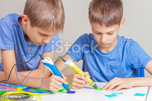 899701486 istock photo Two boys creating with 3d printing pens 1182932816