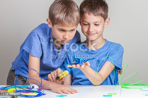 1082038948 istock photo Two boys creating with 3d printing pens 1191894691