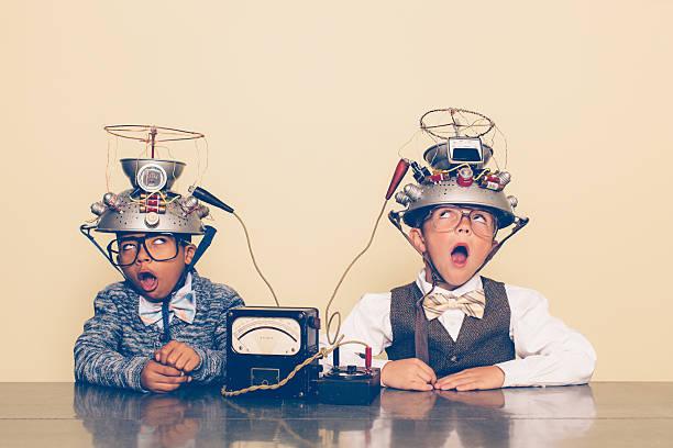 Dos niños vestido como nerds experimentar con cascos mente de lectura - foto de stock