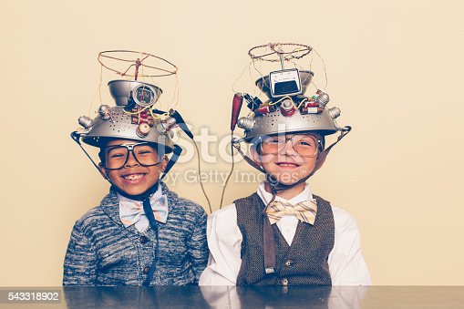 Two nerd boys dressed in casual clothing, glasses and bow ties experiment with a homemade science project. They are smiling and sitting at a table with helmets on their heads in front of a beige background. Retro styling.