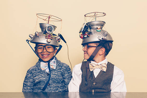 two boys dressed as nerds smiling with mind reading helmets - genius stock photos and pictures