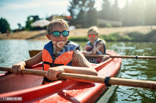 Two boys enjoying kayaking on lake on sunny summer day. Nikon D810