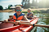 Two boys enjoying kayaking on lake on sunny summer day.\nNikon D810