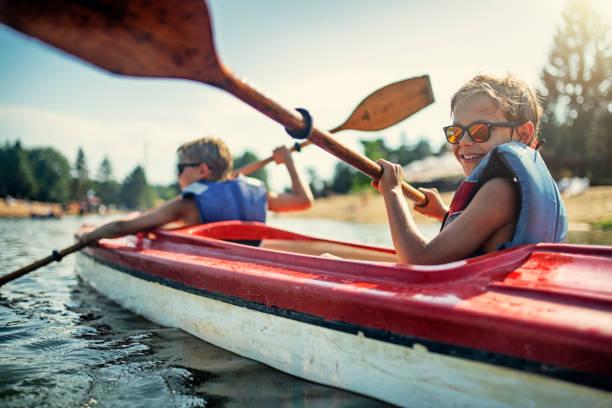 dois meninos que apreciam kayaking no lago - esporte aquático - fotografias e filmes do acervo