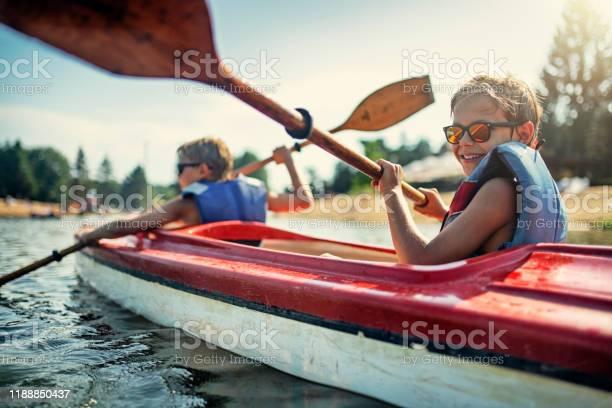 Photo of Two boys enjoying kayaking on lake