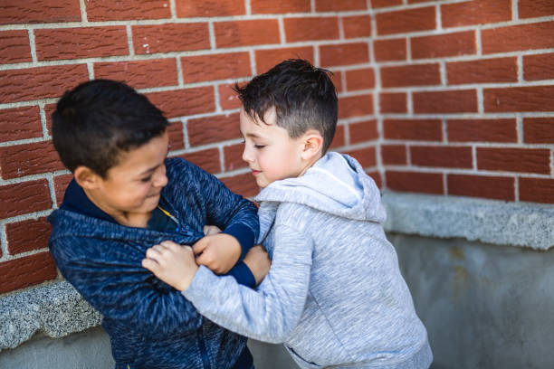 two boys fighting in playground - fighting stock photos and pictures