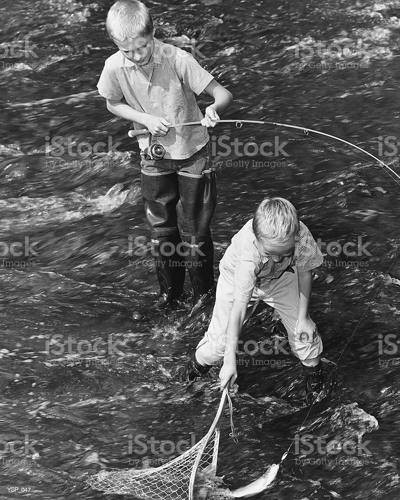 Two boys fishing; one catching fish in net 免版稅 stock photo