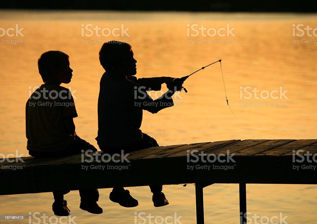 Two Boys Fishing Silhouette stock photo