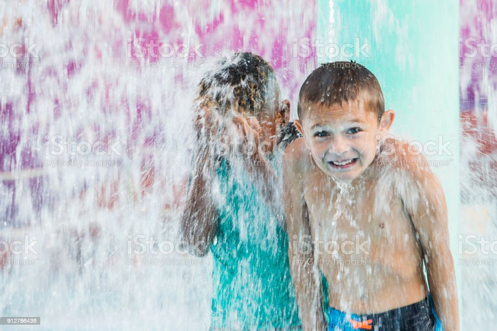 Two boys getting drenched at water park stock photo