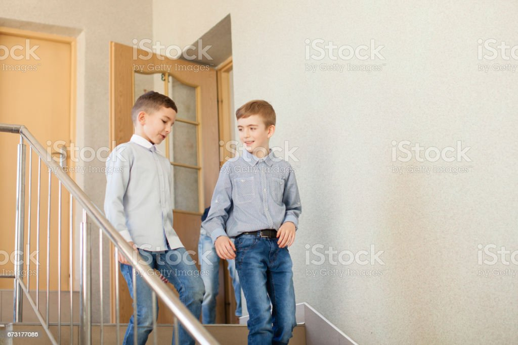 Two boys go downstairs stock photo