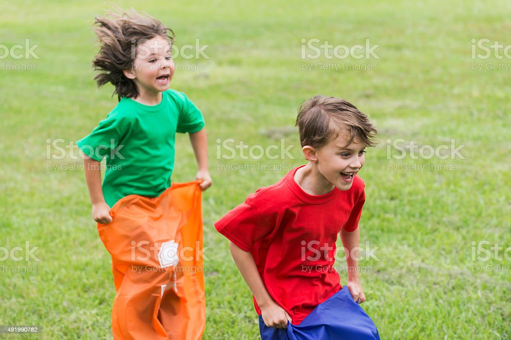 Two boys having fun competing in potato sack race stock photo