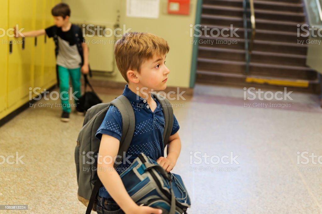 Two boys hurrying around lockers in elementary school. stock photo