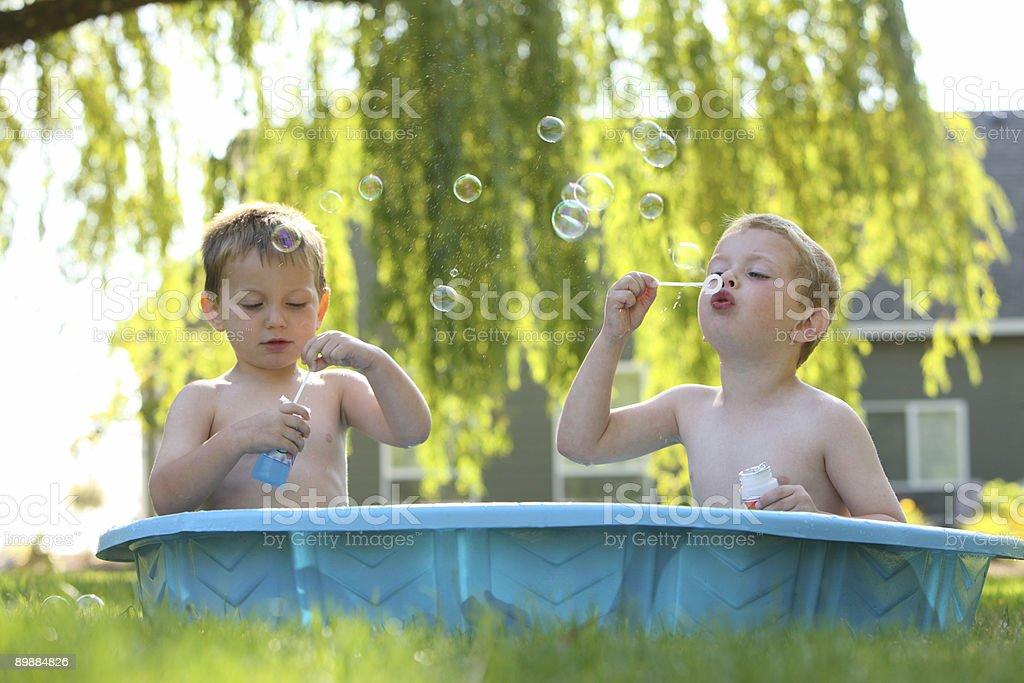 Zwei kleine Jungs Sitzen im pool blowing bubbles Lizenzfreies stock-foto