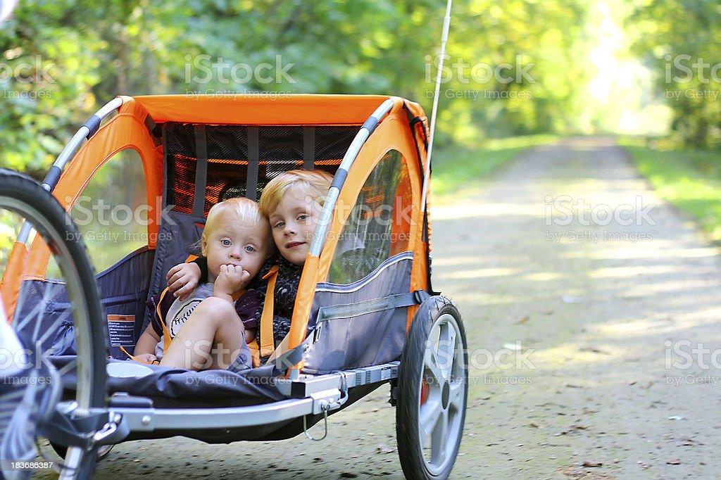 Dos niños en bicicleta remolque al aire libre - Foto de stock de Abrazar libre de derechos