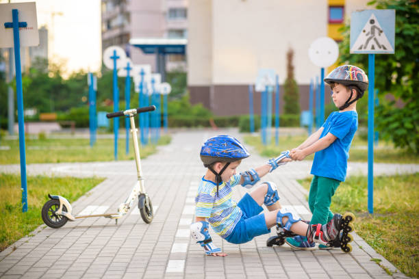 two boys in park, help boy with roller skates to stand up stock photo