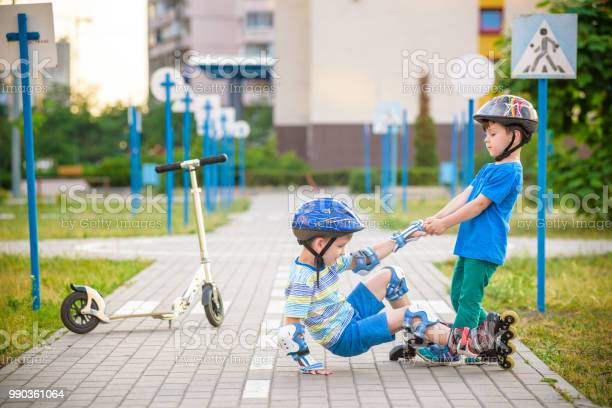 two boys in park, help boy with roller skates to stand up Two boys sibling brothers together in park, helps boy with roller skates to stand up after fall. Friendship and active leisure summer holidays time with family concept. Activity Stock Photo