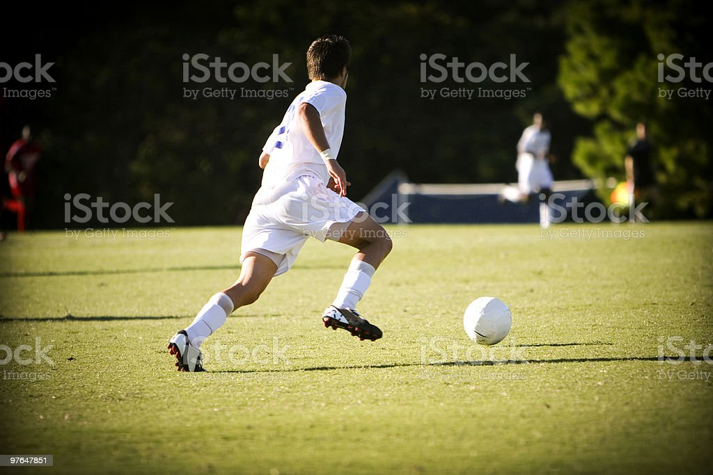 Two boys in white outfits playing soccer in the field stock photo