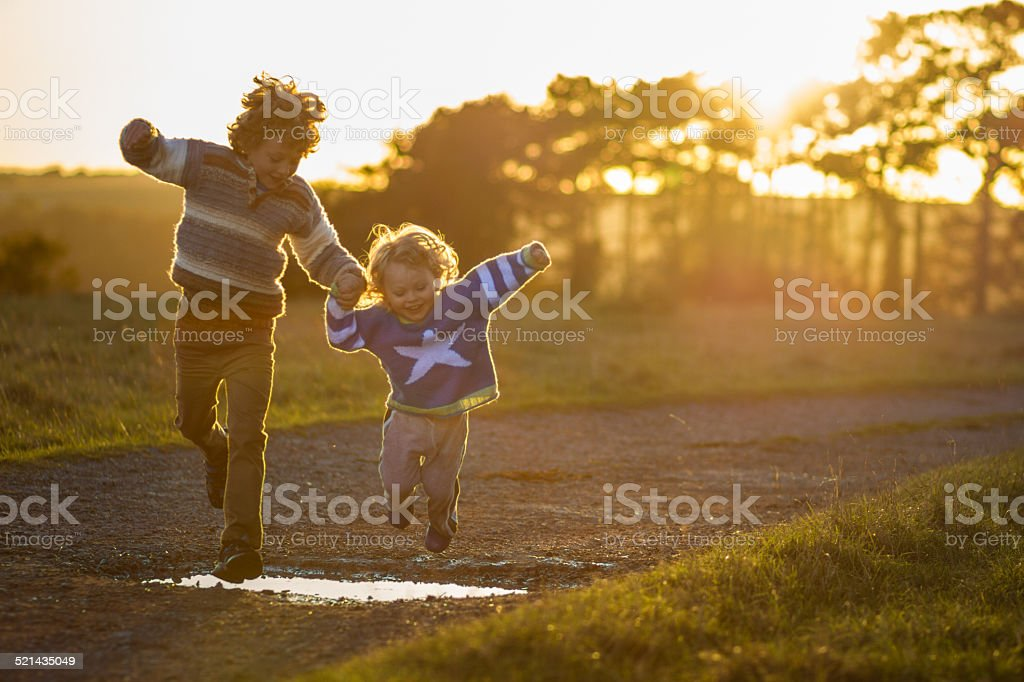 two boys jumping over puddles stock photo