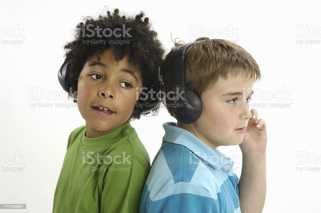 Two boys listening on wireless headphones royalty-free stock photo