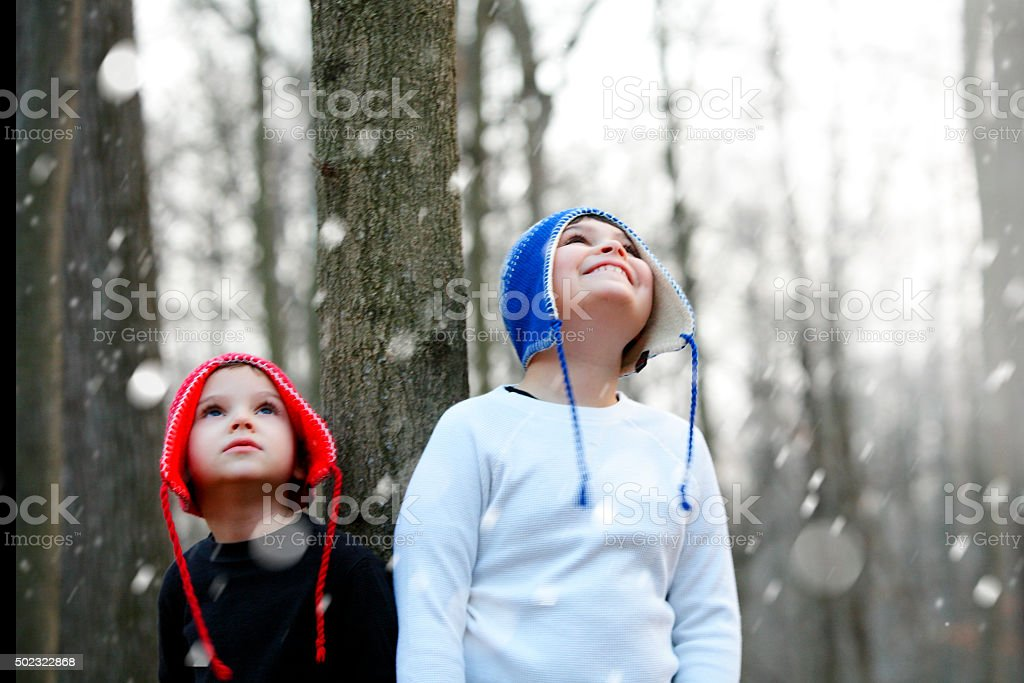 Two boys looking up full of wonder at falling snow stock photo