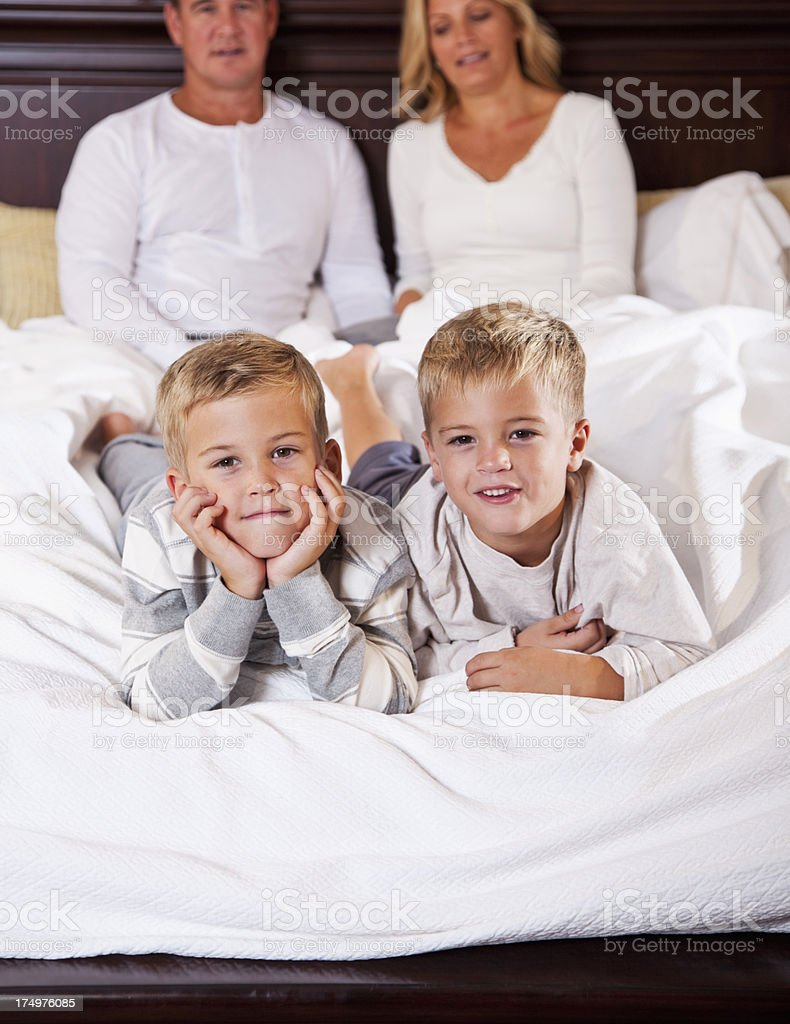 Two boys lying on bed, parents in background royalty-free stock photo