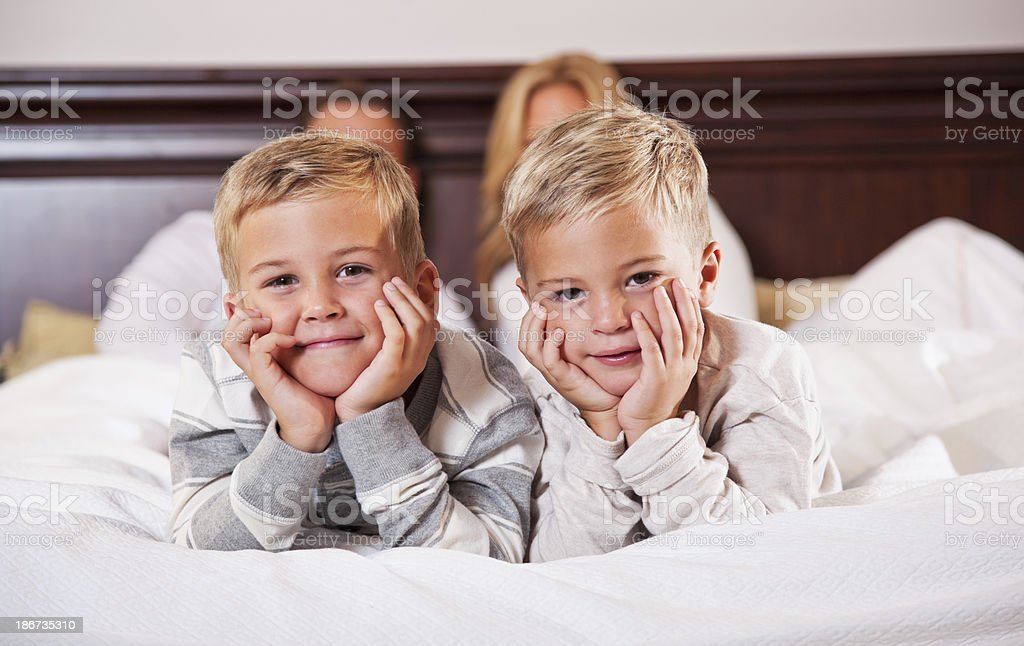 Two boys lying on bed, parents in background stock photo