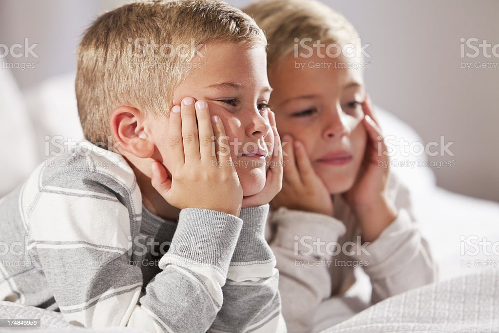 Two boys lying on bed stock photo